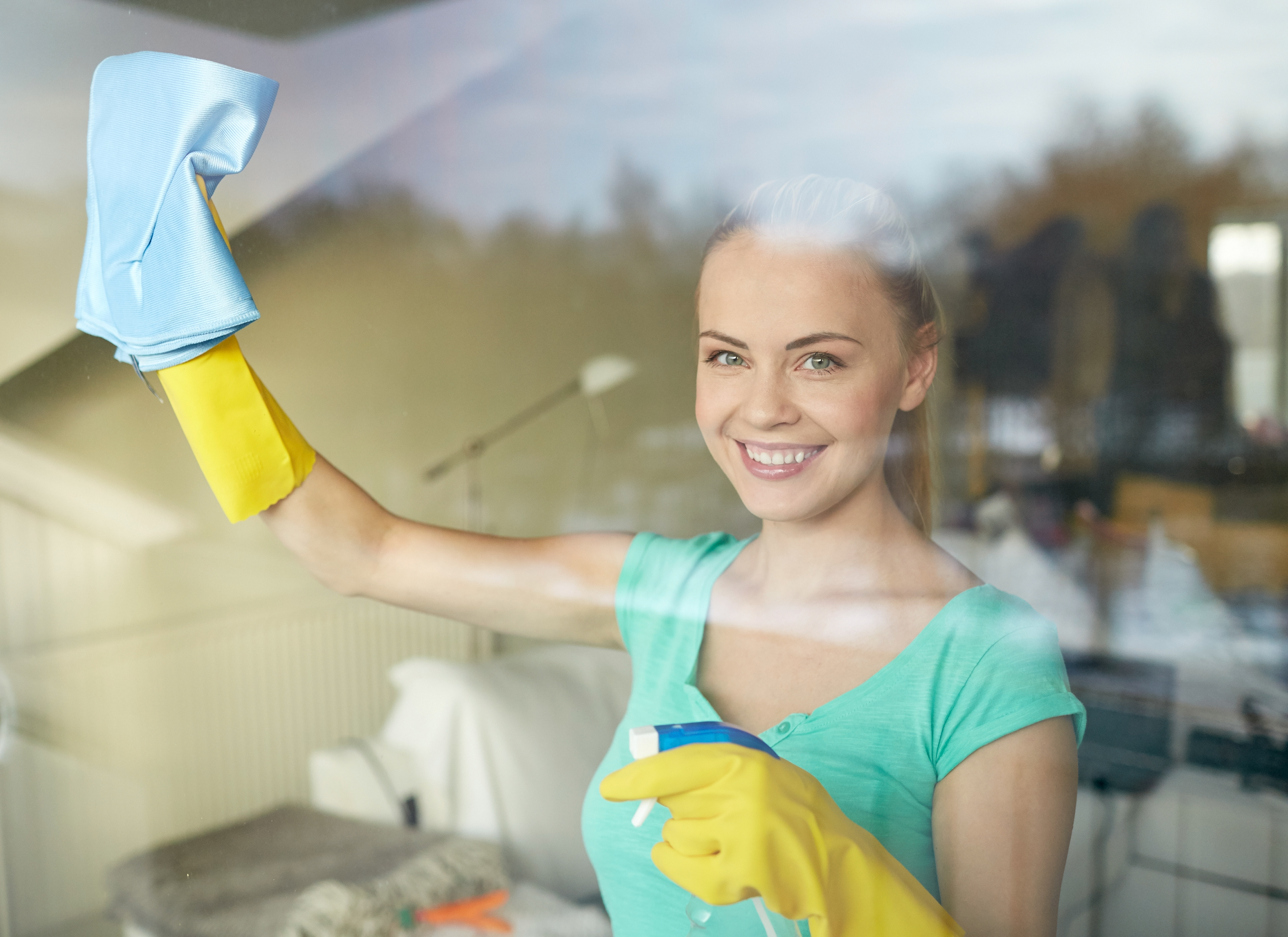 11201577-happy-woman-in-gloves-cleaning-window-with-rag