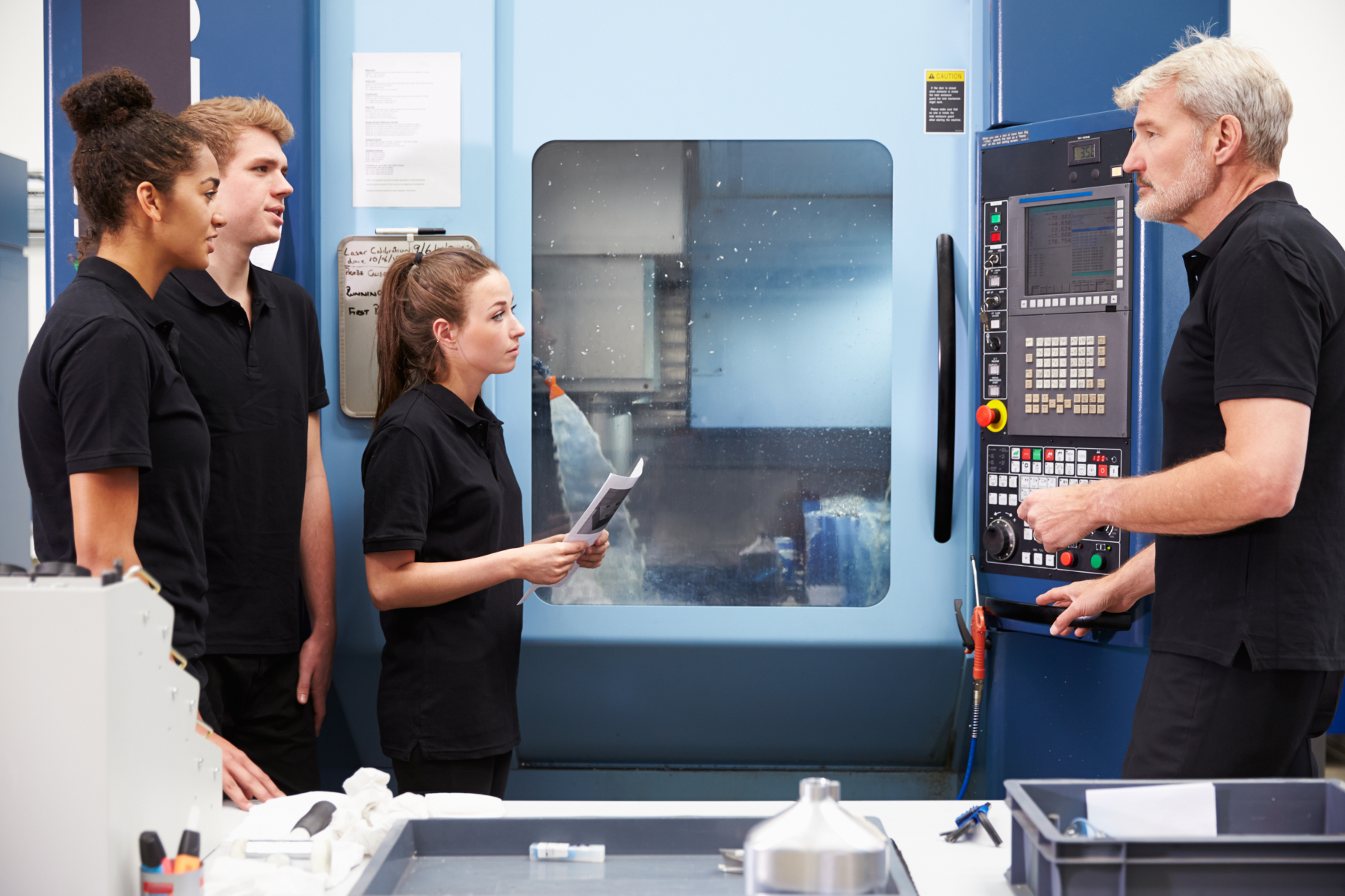 13112869-three-apprentices-working-with-engineer-on-cnc-machinery (003)