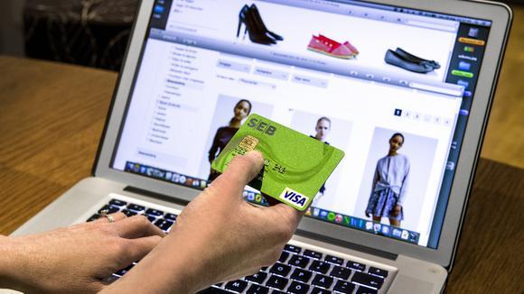 En kund köper skor och kläder på nätet med ett kontokort.