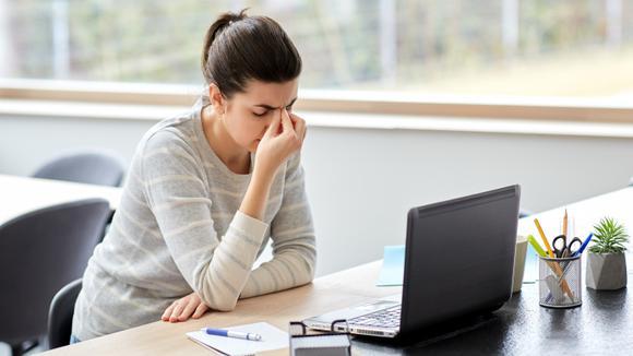 Bekymrad kvinna vid skrivbord och laptop