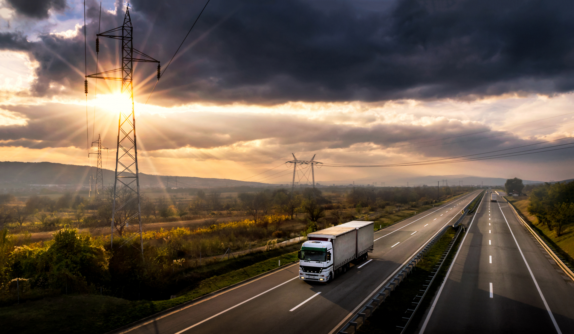 22973649-white-lorry-on-a-highway-at-sunset