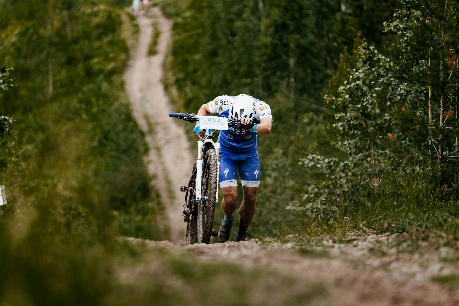 24951500-man-cyclist-with-mountainbike-long-uphill-climbs-during