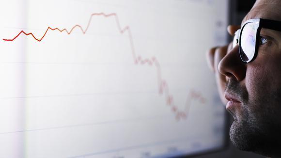 En affärsman som tittar på en skärm med fallande graf