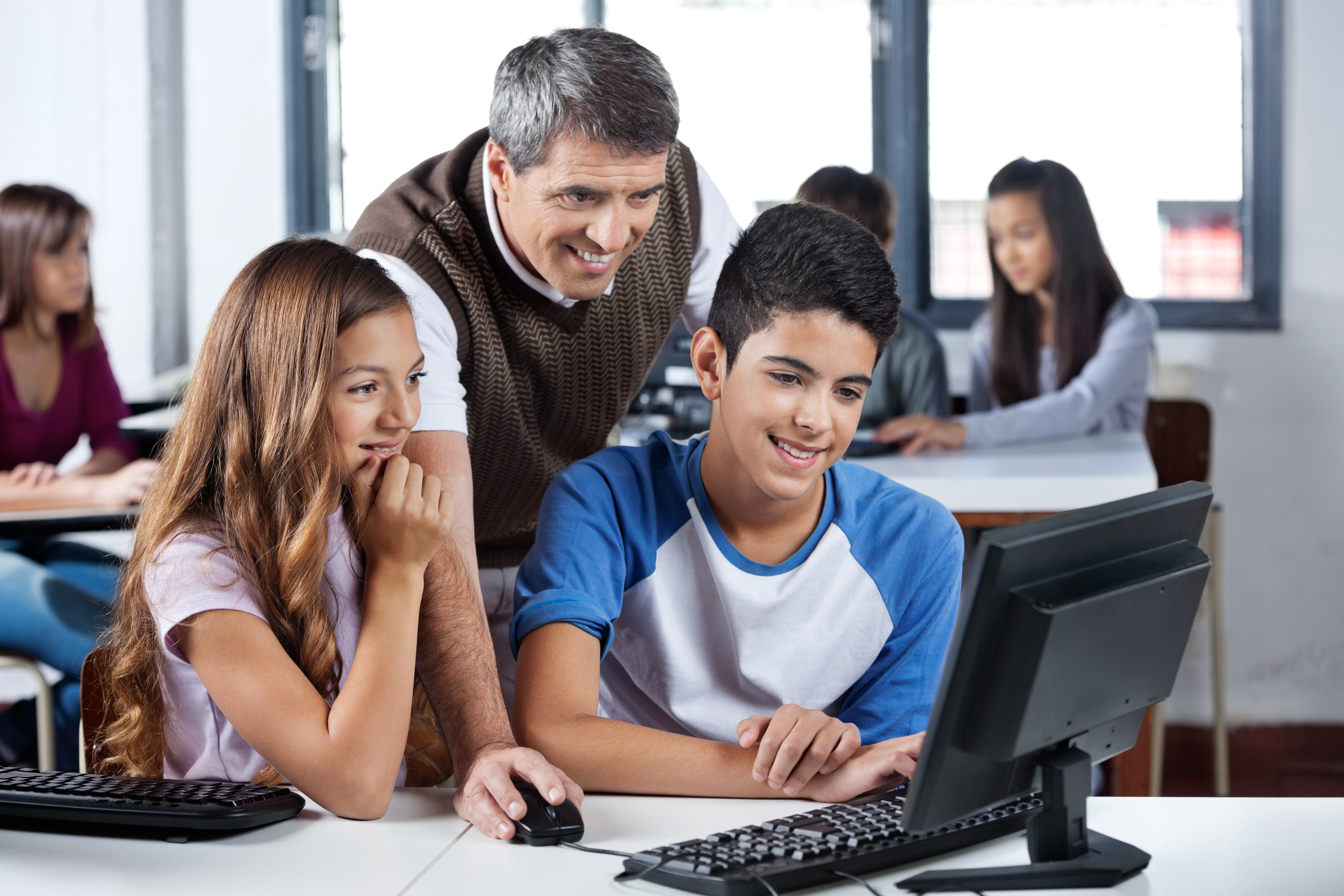 5157859-happy-mature-teacher-and-students-using-computer