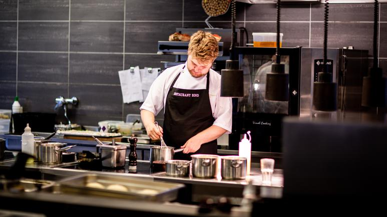 Kock som arbetar i sitt kök