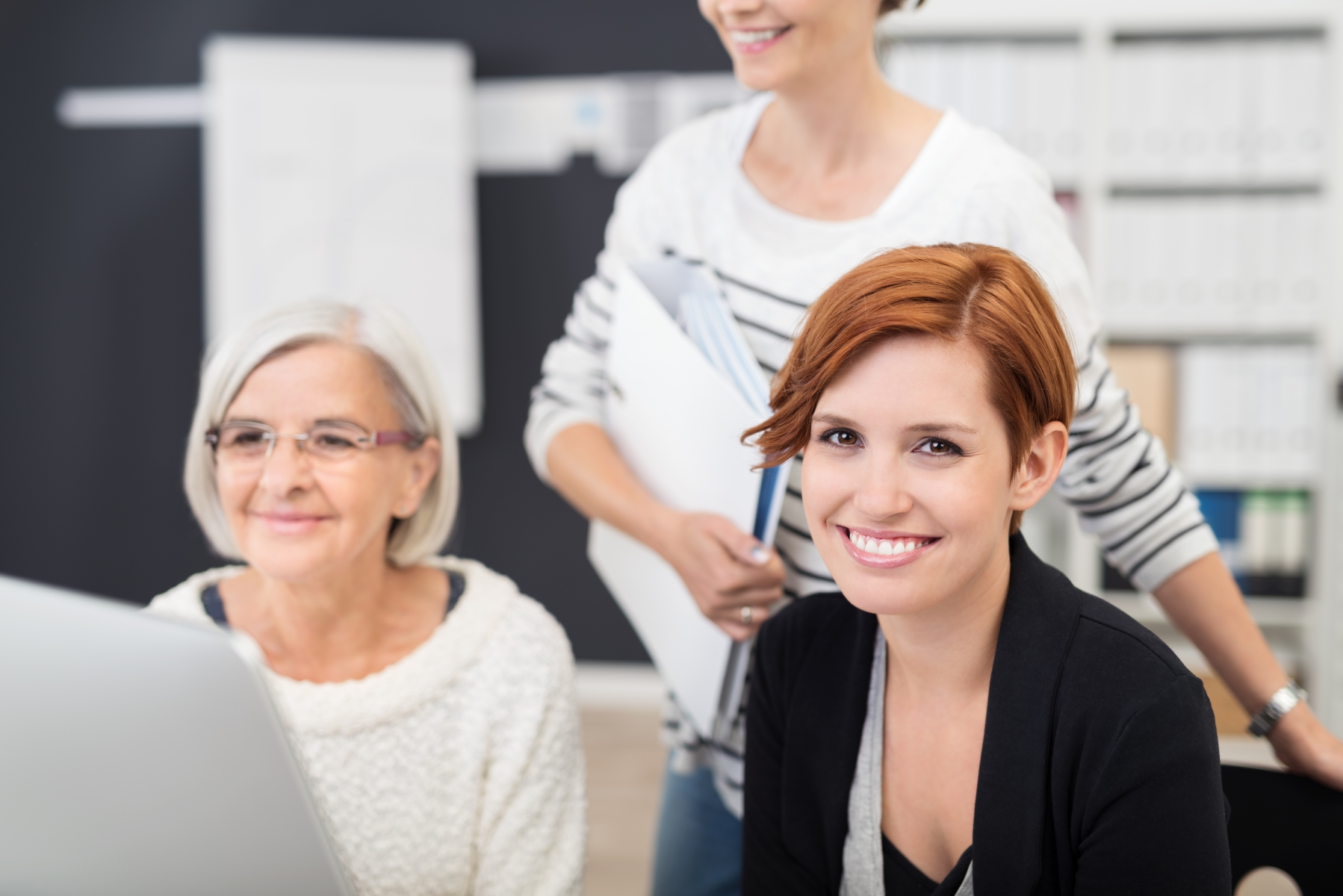 13223959-office-woman-smiles-at-camera-while-in-the-group