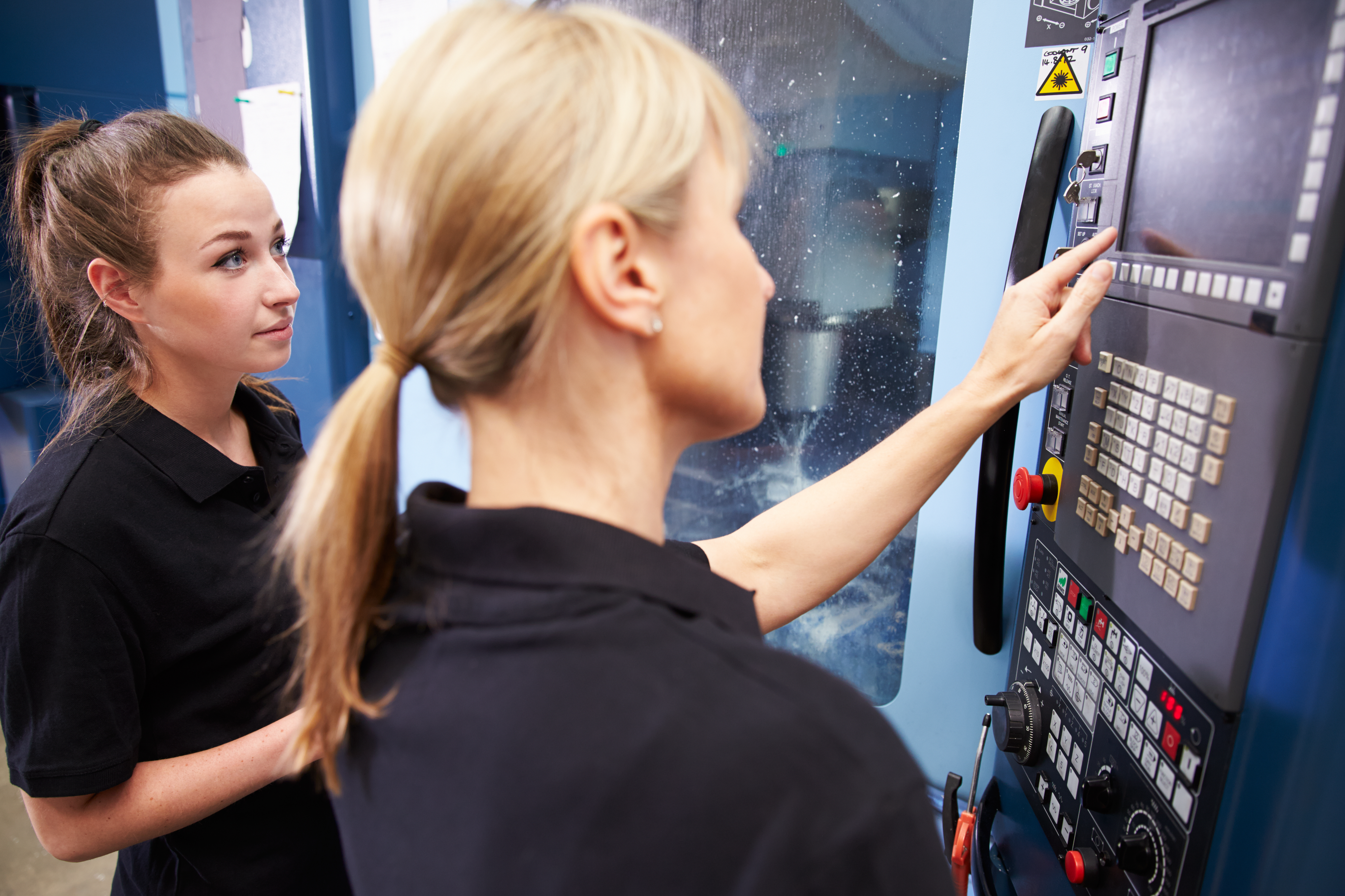 13112881-apprentice-working-with-female-engineer-on-cnc-machinery
