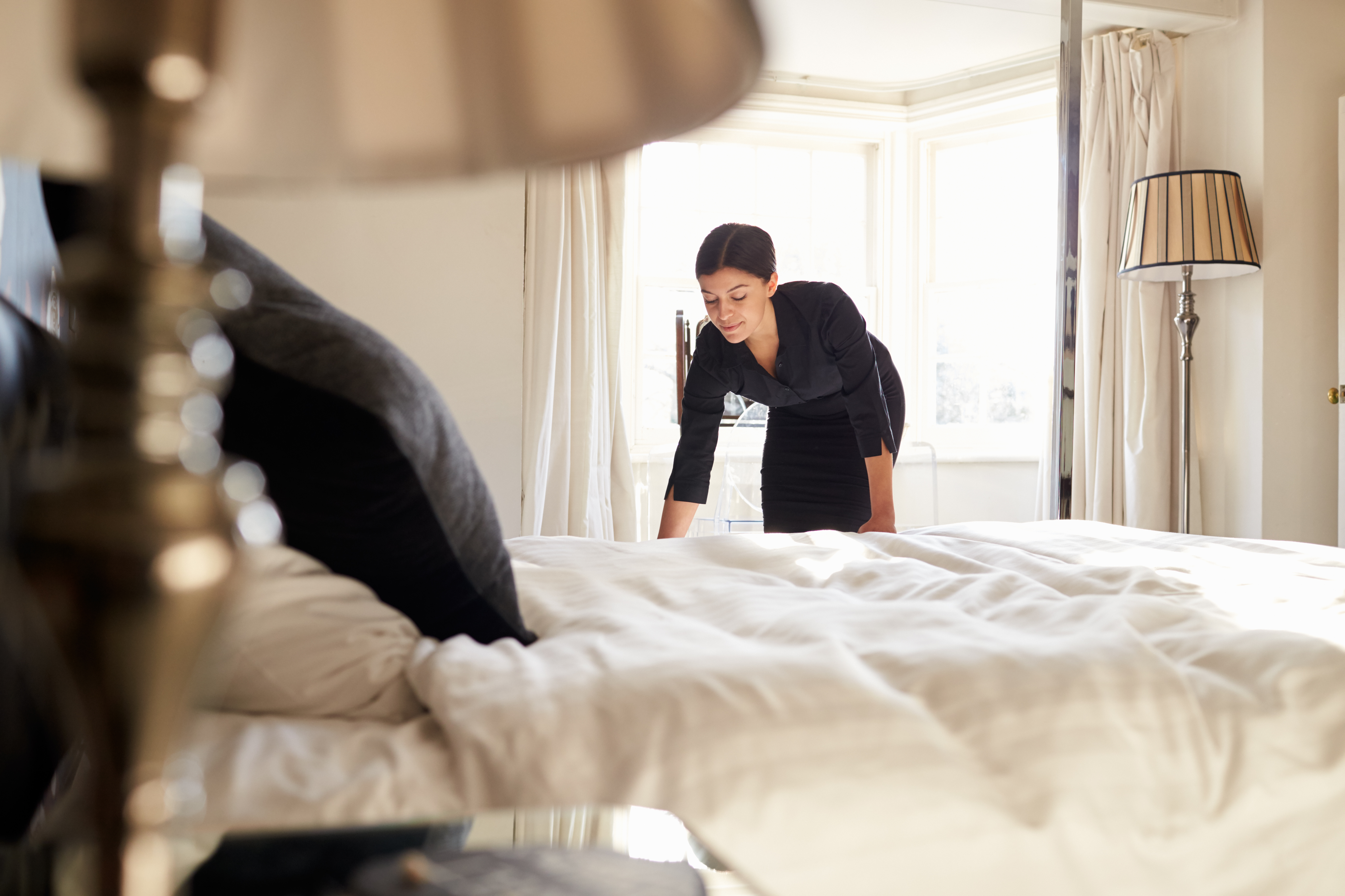 15836541-chambermaid-changing-bed-linen-on-the-bed-in-a-hotel-room